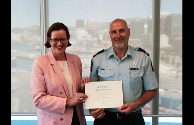 NEW ZEALAND : The photo shows Kirk McPherson receiving his certificate from Comptroller Christine Stevenson. Kirk, from Border Operations, received his certificate for working at the Ministry of Health to support the government's Managed Isolation and Quarantine planning from a Customs perspective, while leading the Wellington team through the COVID-19 response and the beginning of the Maritime Border Order.
