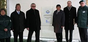 Together with dignitaries, Mr. Julian Würtenberger, Director General of German Customs Administration (left), Mr. Kunio Mikuriya, WCO Secretary General (right), and Mr. Thomas Schoeneck, President of the German Centre for Education and Science of the Federal Revenue Administration (further right), stand next to the board at the entrance of the Dog Training Centre.