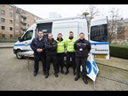 Luxembourg Customs officers stand in front of a mobile scanning van