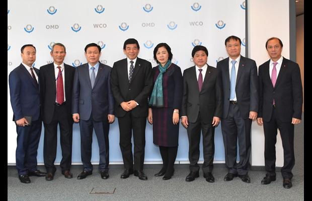 Secretary General Kunio Mikuriya and the Deputy Prime Minister of Vietnam, H.E. Mr. Vuong Dinh Hue, at WCO Headquarters, surrounded by Officials
